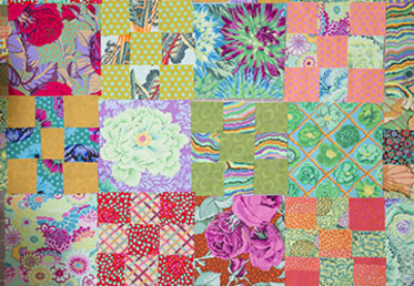 Kaffe Fassett mocks up a layout on his trademark design wall, working with prints in different scales to achieve a version of his classic pattern in a leafy, misty spring mood.