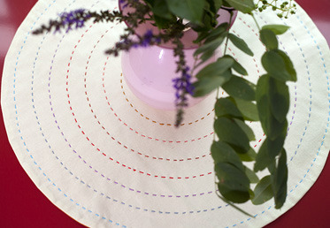 Anna Maria Horner puts her contemporary take on the traditional doily. She shows you how to create a reversible doily with concentric rings of running stitches in a beautiful spectrum.