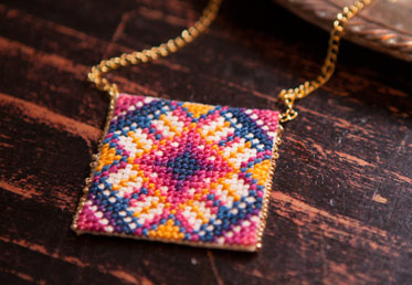 Anna Maria makes cross-stitch modern with this pendant, worked up in one of her signature bright palettes. The small scale makes this project terrific for new cross stitchers.