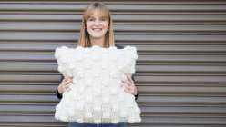 Beth from Wool And The Gang holding the Impossible Dreamer cushion, knit in sumptuous Crazy Sexy Wool on oversized needles.