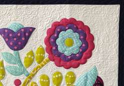 Sue Nickels shares her signature technique for assembling a vibrant, floral appliqué quilt top. Each piece of appliqué uses just a bit of fusible web to keep it in place, and is then secured permanently with machine blanket stitching.